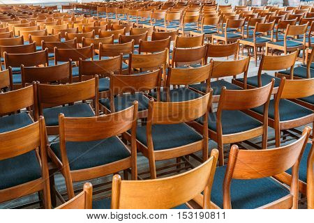 Many Empty The Same Wooden Chairs With Backrest And Blue Upholstery Standing In Neat Rows In Large Auditorium.