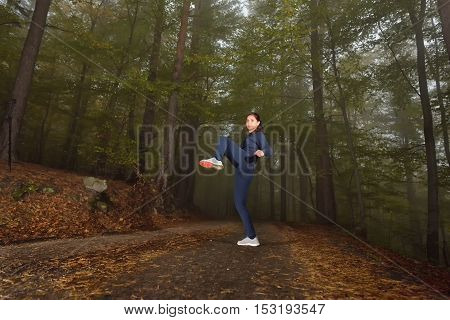 Girl doing knee kick exercise during kickboxing training in a misty autumn forrest