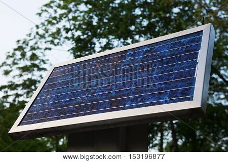Solar energy pannel, eco battery on green leafs background. Eco power technology in real life. Green energy concept.