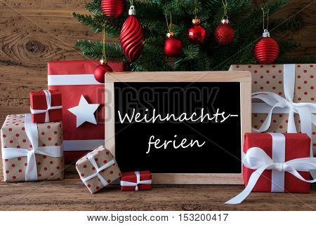 Colorful Christmas Card For Seasons Greetings. Christmas Tree With Red Balls. Gifts Or Presents In The Front Of Wooden Background. Chalkboard With German Text Weihnachtsferien Means Christmas Holidays