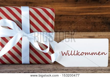 Macro Of Christmas Gift Or Present On Wooden Background. Card For Seasons Greetings, Best Wishes Or Congratulations. White Ribbon With Bow. German Text Willkommen Means Welcome