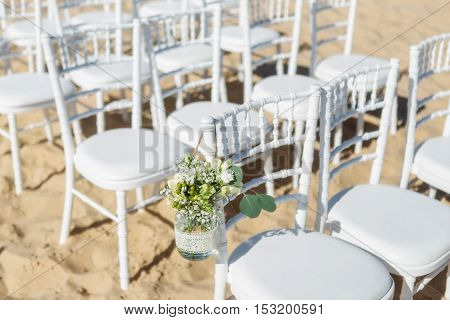 Bunch of flowers in a vase for a wedding ceremony. Against the background of chairs for guests.