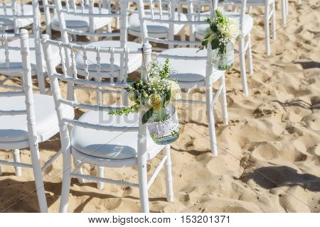 Decoration flowers for a wedding ceremony. Chairs for guests.