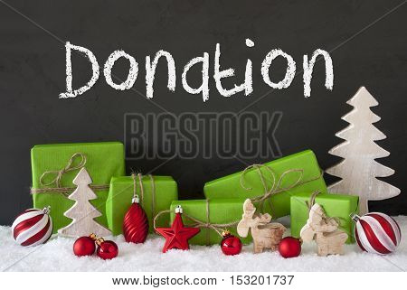 English Text Donation. Green Gifts Or Presents With Christmas Decoration Like Tree, Moose Or Red Christmas Tree Ball. Black Cement Wall As Background With Snow.