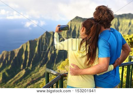 Happy interracial travel couple taking selfie picture with phone at na pali coast viewpoint in Kauai, Hawaii with amazing scenic landscape. Famous destination Kalalau Lookout hawaiian attraction.