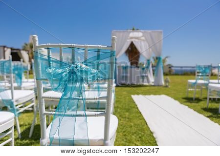 Decoration bow ribbon for a wedding ceremony. Chairs for guests.