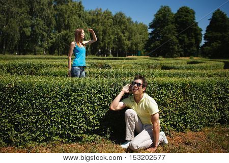 Picture of happy couple playing at hide and seek all together in park. Man and woman spending their weekends or holidays outdoors.