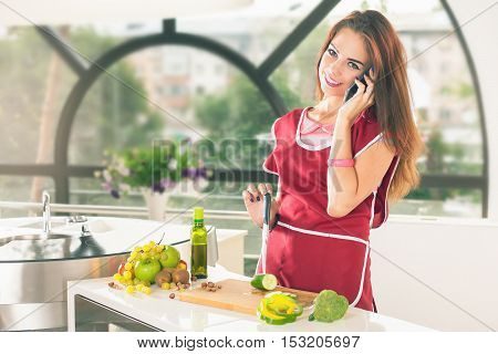 Attractive girl cooking and talking by mobile phone with friend. Dressed in apron. Fresh fruits and vegetables at the table at kitchen. Diet. Healthy food ingredients. Recipe. Cutting board. Nutrition