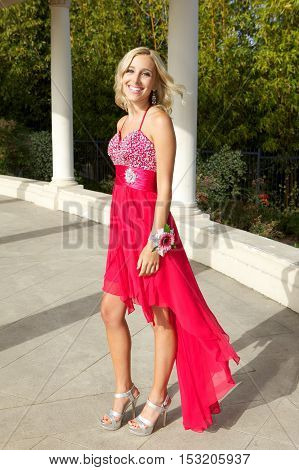 Beautiful Blonde Teenage Girl Going to the Prom Posing Outside in her red dress.