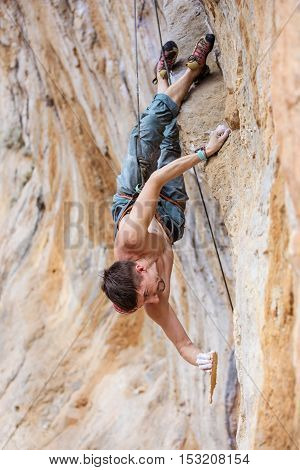 Male rock climber gripping a chipped off piece of cliff while climbing a natural cliff