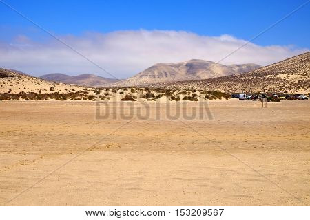 The beach Sotavento in Fuerteventura the sand dunes and the hills with mixed sand and rock: golden and black in a sunny day.