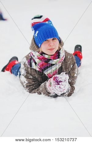 Funny girl in hat and striped scarf lying on the snow and smiling.