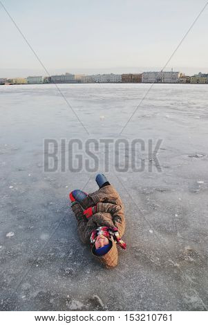 Naughty laughing teen girl in a plaid jacket with a hood lying on a smooth and transparent ice of the Neva river on the background of St. Petersburg's waterfront