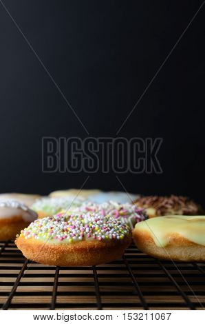 Decorated Mini Doughnut Cakes On Cooling Rack With Black Background