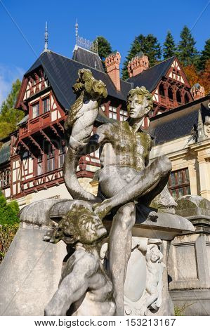 Statue in front of beautiful Peles castle and ornamental garden in Sinaia, Romania, between Valachia and Transylvania