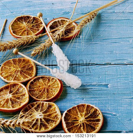Dried orange slices and sugar sticks on a blue wooden table background