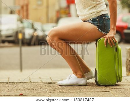 Travel and journey. Part body of female tourist traveller. Girl with green luggage suitcase baggage travelling visiting.