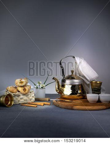 metal tea, cakes and vanilla on dark background