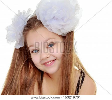 Caucasian long-haired little girl with big white bows on the head . She smiles at the camera. Close-up.Isolated on white background.
