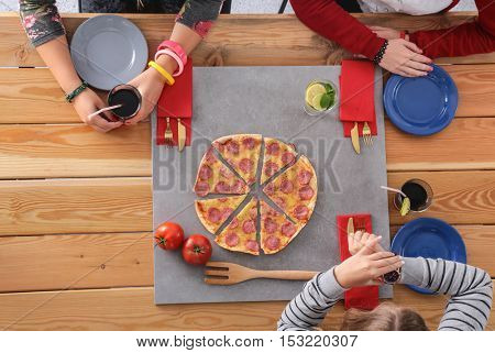 Group of young people eating pizza at desk.