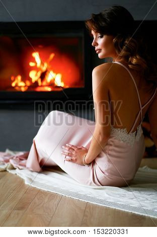 Beautiful woman sitting by the fireplace . Classic interior. Beauty, fashion
