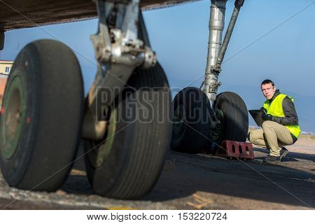 Male engineer checking airplane's wheels before flight