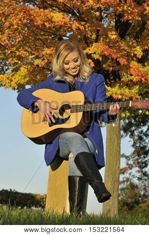 Beautiful Asian woman playing guitar outside during fall season