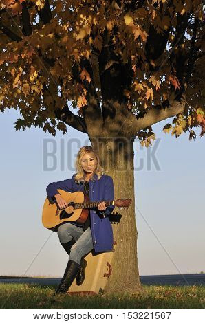 Beautiful Asian woman leaning on tree and playing the guitar