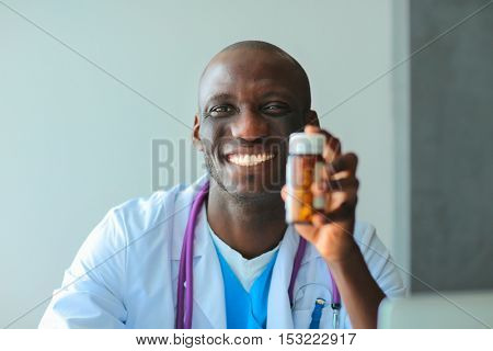 Close-up of male doctor giving jar of pills to patient.