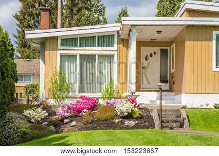 Entrance of beautiful family house with green lawn of front yard in suburban area of Vancouver Canada