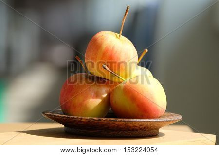 apple place on the wood plate on the wood table