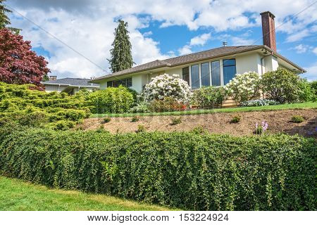 Average family house with rhododendron flowers in front on cloudy sky background. Inexpensive family house on sunny day in British Columbia Canada