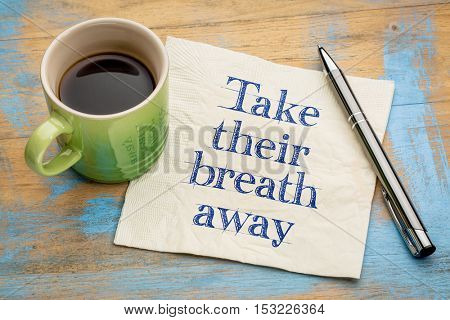 Take their breath away - handwriting on a napkin with a cup of espresso coffee
