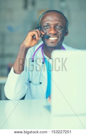 Portrait of young male doctor wearing headset while using computer at desk in clinic
