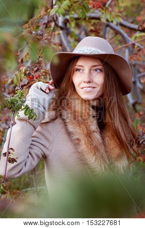 Cute redhead woman with freckles among romanberry bushes in autumn outdoors wearing fedora hat and fur collar beige coat