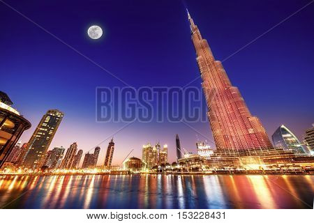 DUBAI, UAE - FEBRUARY 17: Burj Khalifa and fountain - world's tallest tower at 828m at night with moon light, located in Downtown Dubai, Burj Dubai on February 17, 2016 in Dubai, United Arab Emirates