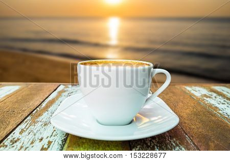 Close up coffee cup on wood table at sunset or sunrise beach.