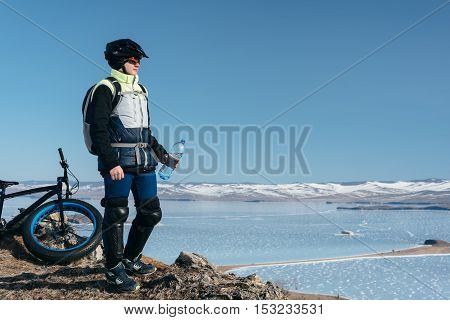 Fat bike also called fat bike or fat-tire bike - Cycling on large wheels. Teen rides a bicycle through the snow mountains in the background.
