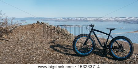 Fatbike also called fat bike or fat-tire bike - Cycling on large wheels. Bike stands on top of the mountain, amid the scenic frozen Lake Baikal.