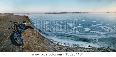 Fatbike also called fat bike or fat-tire bike - Cycling on large wheels. Traveller cyclist sits on a hillside. He is resting on a trip looking at the sunset and very beautiful frozen Lake Baikal.