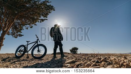 Fatbike also called fat bike or fat-tire bike - Cycling on large wheels. Traveller cyclist stands on the shore of the lake, amid picturesque frozen Lake Baikal and a huge pine tree.