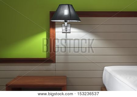mood lighting or lamp at brown headboard wood on the white bed and wooden table with green wall in the room