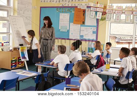 Schoolgirl writing on flip chart at the front of class