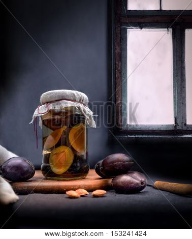 plum jam and fresh plums on a background of a window