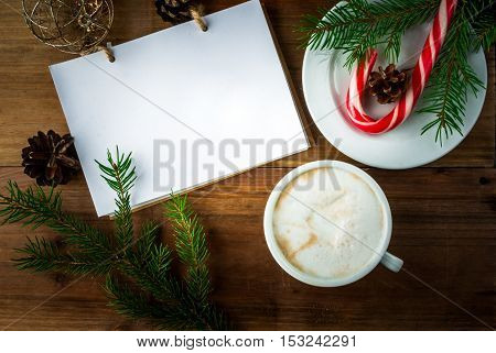 Christmas coffee latte or cappuccino with a notebook for list of gifts or a wishlist, Christmas tree branch, pine cones and Christmas balls, copy space