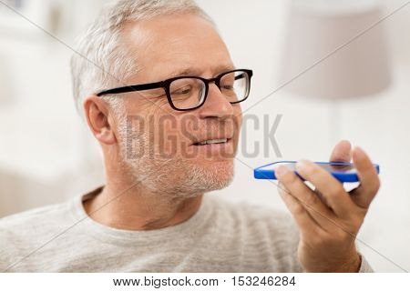 technology, people, lifestyle and communication concept - close up of happy senior man using voice command recorder or calling on smartphone at home