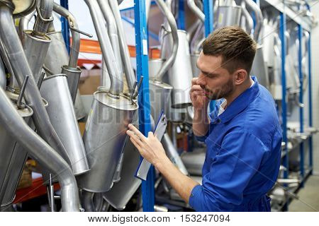 car service, repair, maintenance and people concept - auto mechanic man or smith with clipboard and mufflers calling on phone at workshop warehouse