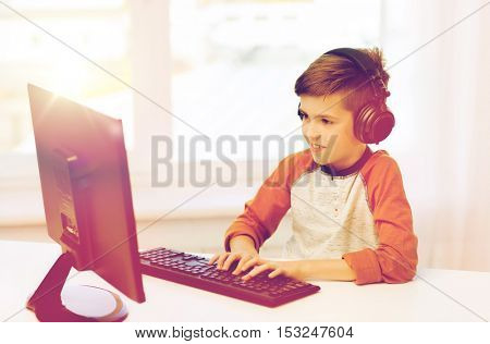 leisure, education, children, technology and people concept - happy boy with computer and headphones typing on keyboard or playing video game at home