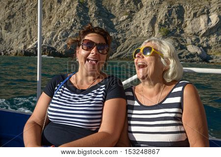 Two Laughing Women Are On Motor Boat On Cliff Background.