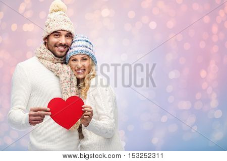 love, valentines day, couple, christmas and people concept - smiling man and woman in winter hats and scarf holding red paper heart shape over rose quartz and serenity lights background